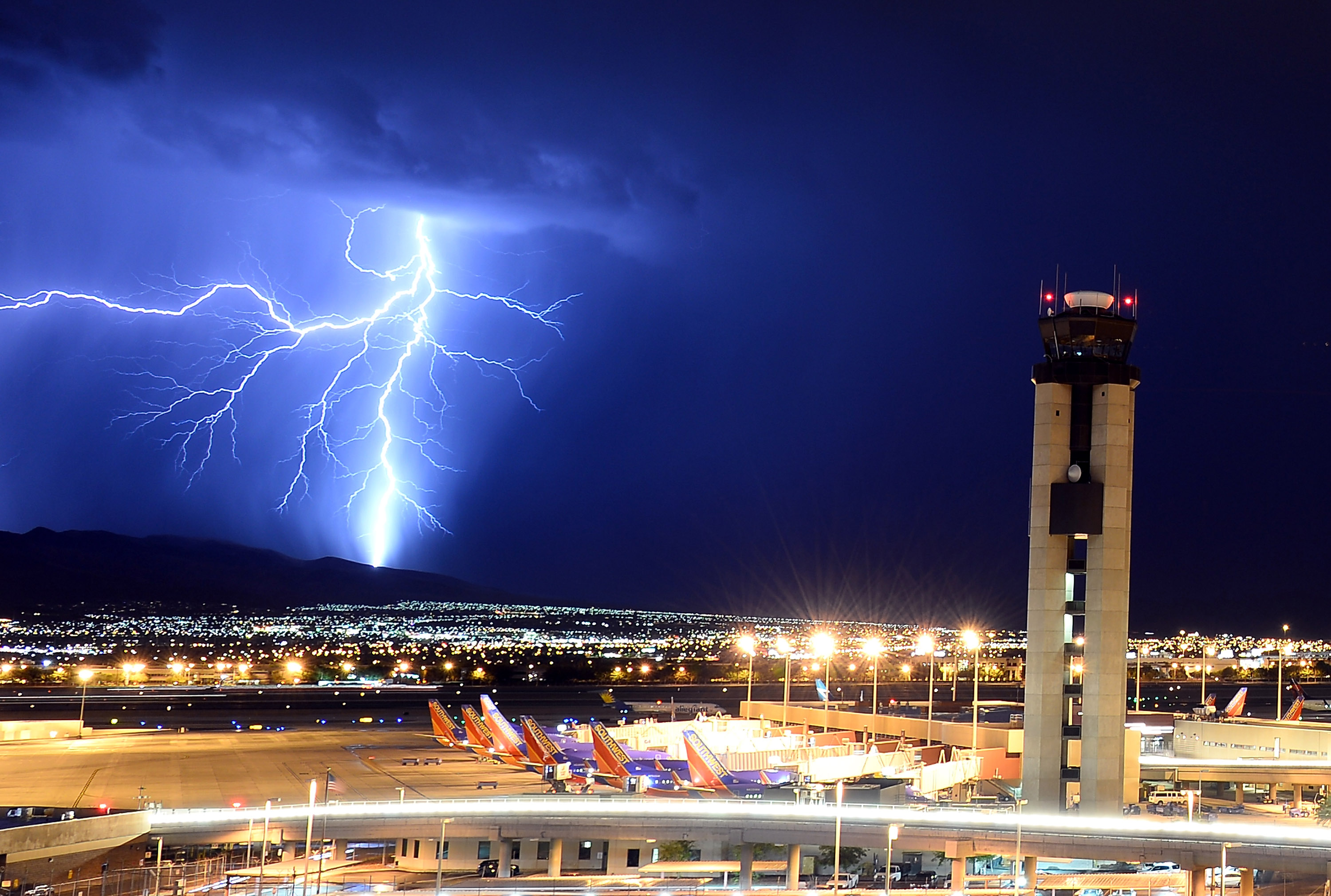 Slide 7 of 20: LAS VEGAS, NV - AUGUST 18: Lightning flashes behind an air traffic control tower at McCarran International Airport on August 18, 2013 in Las Vegas, Nevada. Thunderstorms swept across the area on Sunday prompting the National Weather Service to issue multiple severe thunderstorm and flash flood warnings. (Photo by Ethan Miller/Getty Images)