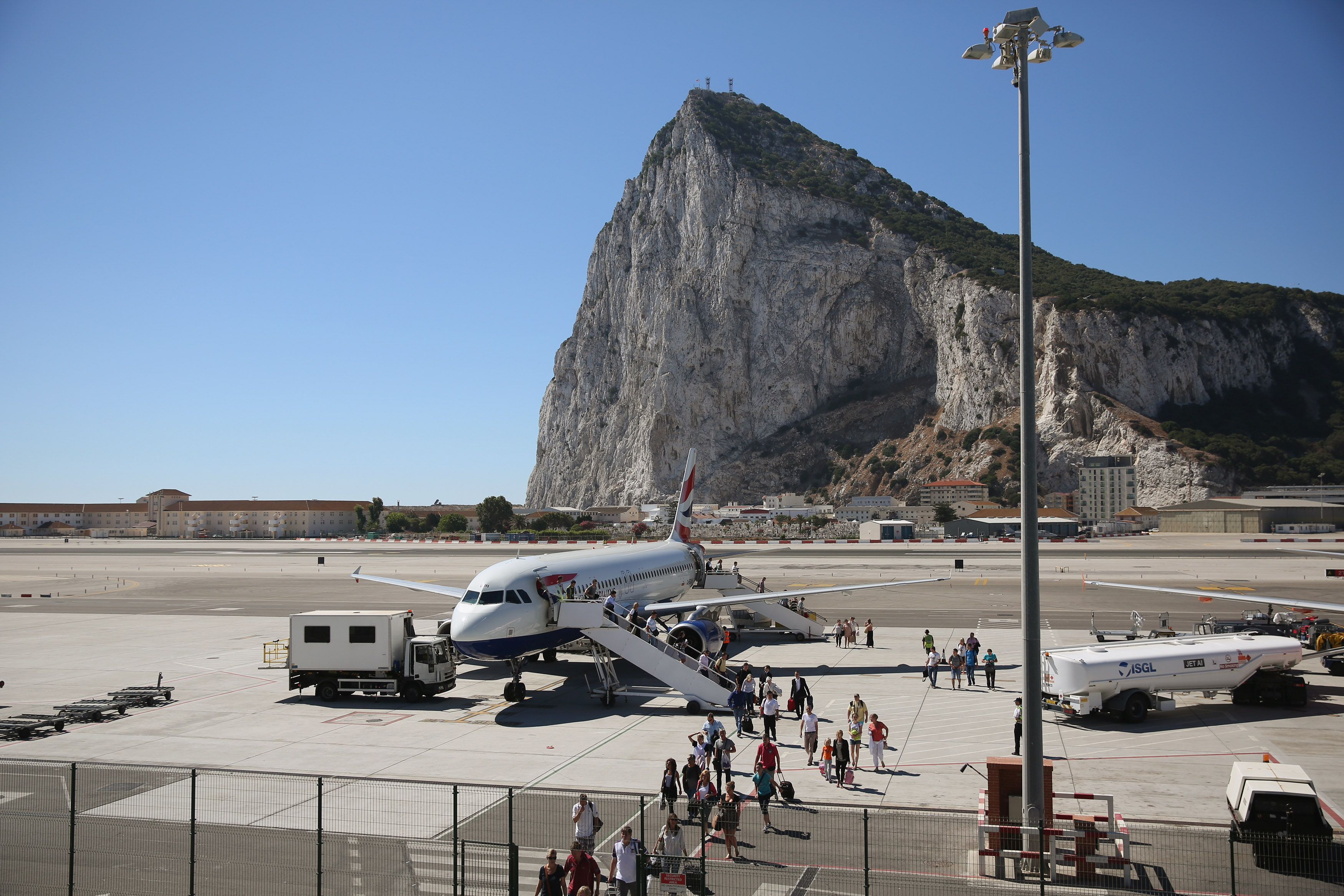Slide 14 of 20: GIBRALTAR - AUGUST 08: Passengers disembark a flight shortly after landing at Gibraltar International Airport on August 8, 2013 in Gibraltar. David Cameron has spoken with his Spanish counterpart, Mariano Rajoy, and Mr Rajoy has offered to 'reduce measures' at the Gibraltar border. Tensions between the British and Spanish governments have been raised on issues surrounding the sovereignty of Gibraltar. An increase in Spanish border crossing checks between the Rock and mainland Spain, leading to lengthy queues, is widely considered to be a retaliatory move for the construction of an artificial reef in British waters, which it is claimed has had a negative impact on Spanish fishing vessels in the area. (Photo by Oli Scarff/Getty Images)