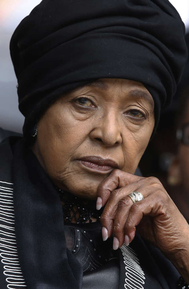 FILE - In this Tuesday, Dec. 10, 2013 file photo Winnie Madikizela-Mandela, Nelson Mandela's former wife, listens to speakers during the memorial service for former South African president Nelson Mandela at the FNB Stadium in Soweto near Johannesburg. South African state broadcaster SABC said Monday April 2, 2018, that anti-apartheid activist Winnie Madikizela-Mandela has died. (AP Photo/Matt Dunham, File)