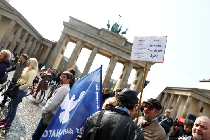 A protester holds a poster during the demonstration against airstrikes on Syria in Berlin, Germany.