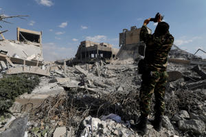 A Syrian military officer records a video inside the destroyed Scientific Research Centre in Damascus, Syria April 14, 2018.