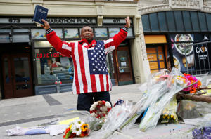 Cristopher Nzenwa, of Boston, prays at the site of the first explosion during the 2013 Boston Marathon on April 15, 2018, in Boston.
