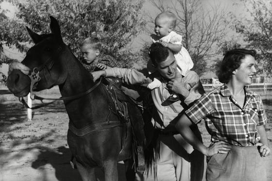 Slide 3 of 28: George H. W. Bush with his wife, Barbara, and their children Pauline and George W. on horse in the yard of their Midlands, Texas ranch circa 1950.