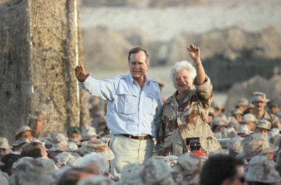 Slide 13 of 28: Pres. George H. W. Bush, left, and First Lady Barbara Bush wave to U.S Marines at the desert encampment during a thanksgiving visit, Thursday, Nov. 22, 1990, Saudi Arabia.