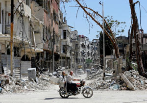 TOPSHOT - Syrians ride a motorbike along a destroyed street in Douma on the outskirts of Damascus on April 16, 2018 during an organised media tour after the Syrian army declared that all anti-regime forces have left Eastern Ghouta, following a blistering two month offensive on the rebel enclave.   The announcement, which represents a key strategic victory for President Bashar al-Assad, came just hours after US-led strikes pounded Syrian government targets in response to a suspected chemical attack on the enclave's main town of Douma.  / AFP PHOTO / LOUAI BESHARA        (Photo credit should read LOUAI BESHARA/AFP/Getty Images)