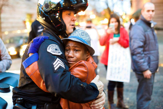 In this Nov. 25, 2014, file photo provided by Johnny Nguyen, Portland police Sgt. Bret Barnum, left, and Devonte Hart, 12, hug at a rally in Portland, Ore., where people had gathered in support of the protests in Ferguson, Mo. Authorities have said two women and three children were killed Monday, March 26, 2018, when their SUV fell from a cliff along Pacific Coast Highway in Mendocino County. Hart is one of the three other children still missing after the vehicle fell off a cliff. He had gained fame when this picture of him hugging the white police officer during the protest went viral.
