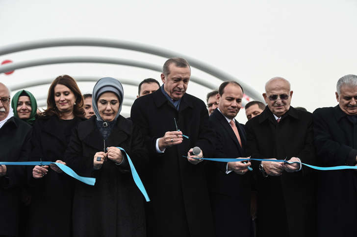 Turkish President Recep Tayyip Erdogan (C), his wife Emine Erdogan (3rdL) and Turkish Prime Minister Binali Yildirim (R) cut the ribbon on December 20, 2016 in Istanbul, during the opening cerenomy of the Avrasya (Eurasia) Tunnel, the first ever road tunnel underneath the Bosphorus Strait in Istanbul from Europe to Asia and the latest project in the Erdogan's plan of transforming Turkey's infrastructure.
