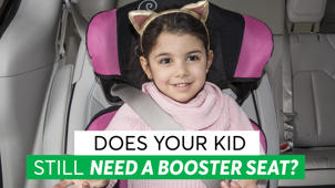 a person holding a sign: Booster Seats: Why Your Big Kid May Still Need a Boost
