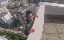 Man does pull-ups on top of a skyscraper