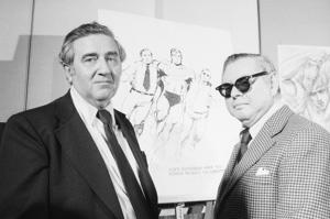 Superman creators Jerry Siegel and Joe Shuster pose in front of sketches of their creation.