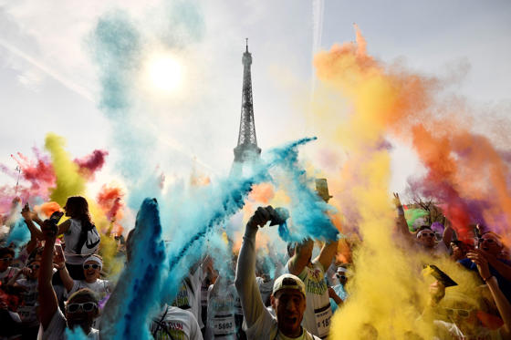 Slide 1 of 37: TOPSHOT - People celebrate at the end of the Color Run 2018 race in front of the Eiffel Tower in Paris, on April 15, 2018. The Color Run is a five kilometres paint race without winners nor prizes, while runners are showered with colored powder at stations along the run. / AFP PHOTO / CHRISTOPHE SIMON        (Photo credit should read CHRISTOPHE SIMON/AFP/Getty Images)
