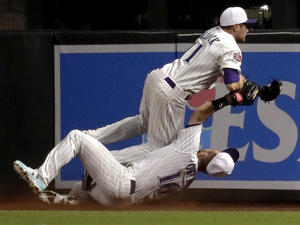 Arizona Diamondbacks Chris Owings (16) catches a fly ball hit by San Francisco Giants' Joe Panik, while colliding with teammate A.J. Pollock during the third inning of a baseball game Thursday, April 19, 2018, in Phoenix. Owings left the game after the play. (AP Photo/Matt York)