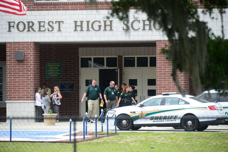 CAPTION: OCALA, FL - APRIL 20: Marion County Police officers walk out Forest High School after a school shooting on April 20, 2018 in Ocala, Florida. It was reported that a former student shot a 17-year-old male student in the ankle The shooter is in custody.