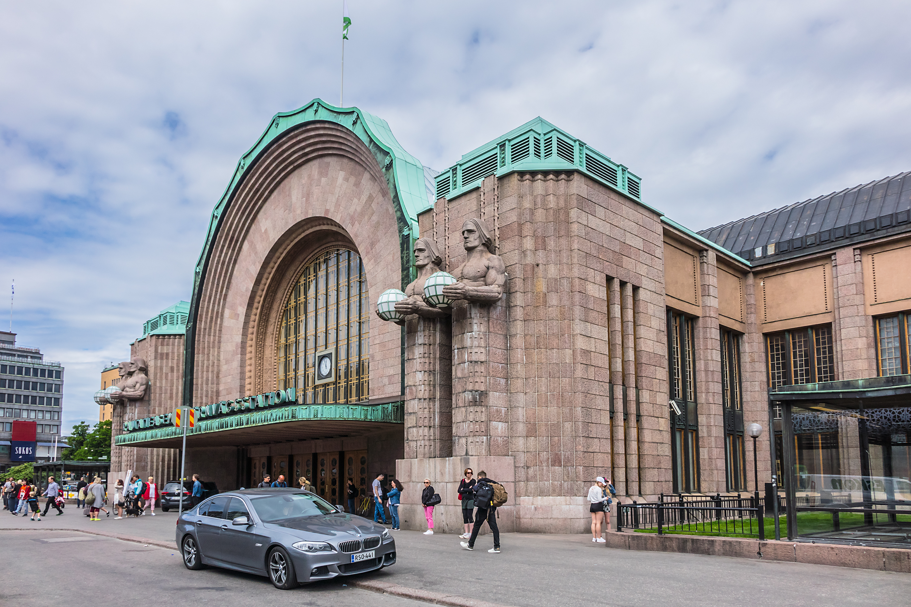Slide 11 of 29: HELSINKI, FINLAND - JUNE 19, 2017: Helsinki Central railway station (Rautatieasema, architect Eliel Saarinen, 1919) with neo classical clock tower and stone figures holding lamps.; Shutterstock ID 676225486; Purchase Order: -