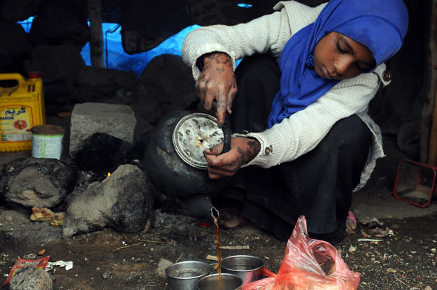 A Girl Pours Hot Beverage Into Metal Glasses At Darwan Refugee Camp In Amran North Of