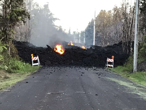 Slide 1 of 20: This photo provided by Hawaii Electric Light shows Mohala Street in Leiliani Estates near the town of Pahoa on Hawaii's Big Island that is blocked by a lava flow from the eruption of Kilauea volcano. The Kilauea volcano sent more lava into Hawaii communities Friday, May 4, 2018