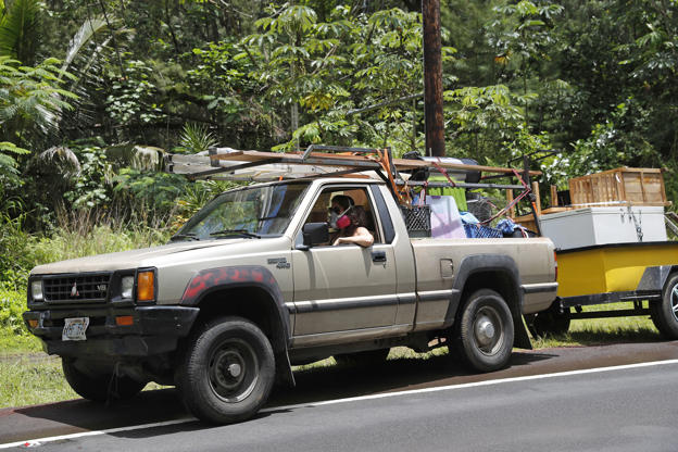 Slide 2 of 66: While wearing an air filter mask, Laura Dawn drives her truck loaded with her possessions as she and her husband flee the lava eruption, Sunday, May 6, 2018, near Pahoa, HI. Their property is just below the active lava eruption and they fear their land will get covered in lava. They are moving further upcoast to a safer area