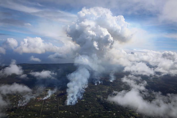 Slide 1 of 66: A plume of gas mixed with smoke from fires caused by lava rises (C) amidst clouds in the Leilani Estates neighborhood in the aftermath of eruptions from the Kilauea volcano on Hawaii's Big Island on May 6, 2018 in Pahoa, Hawaii. A magnitude 6.9 earthquake struck the island May 4. The volcano has spewed lava and high levels of sulfur gas into communities, leading officials to order 1,700 to evacuate. Officials have confirmed 26 homes have now been destroyed by lava in Leilani Estates.