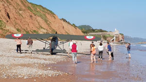 a group of people on a beach: A WWI-era plane near the southern coast of England was forced to make an emergency landing on a beach full of onlookers.