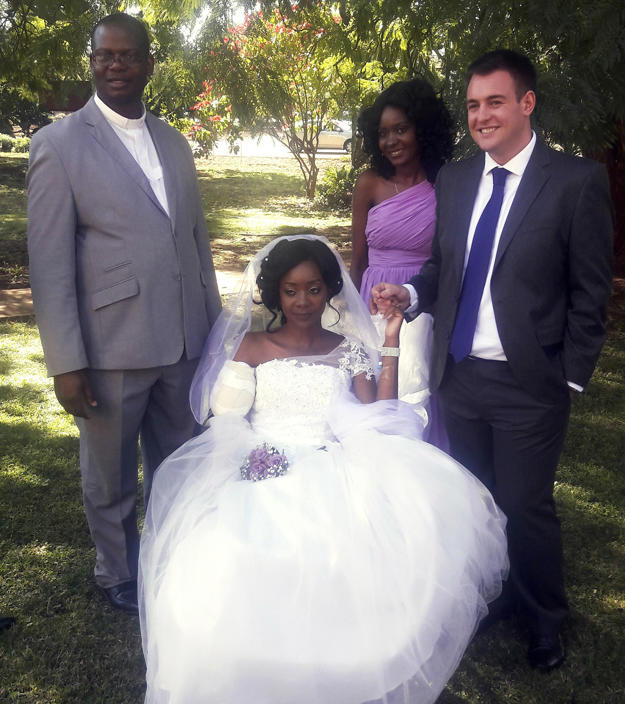 In this photo taken on Saturday, May, 5, 2018, Zenele Ndlovu, center, and Jamie Fox hold hands on their wedding day at a hospital Chapel in Bulawayo, Zimbabwe