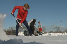 Volunteers help clear snowy field in support of soccer team.