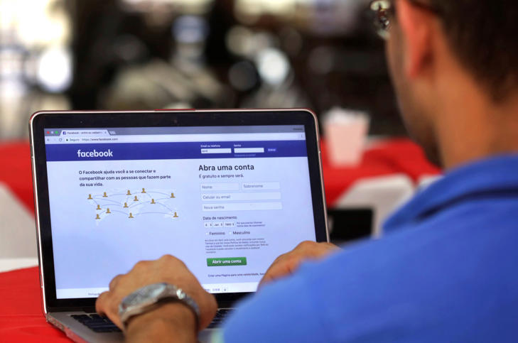 FILE - In this Thursday, Jan. 4, 2018, file photo, a man enters his Facebook page, at a restaurant in Brasilia, Brazil. Federal prosecutors in Latin America's biggest country have opened an investigation to determine if Cambridge Analytica illegally used the profiles of millions of Brazilian Facebook users. (AP Photo/Eraldo Peres, File)