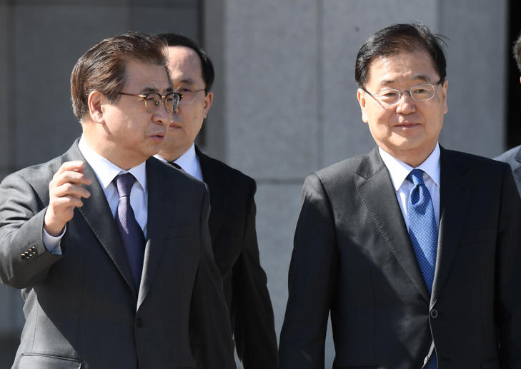 Chung Eui-yong (R), head of the presidential National Security Office, and Suh Hoon (L), the chief of the South's National Intelligence Service, talk before boarding an aircraft as they leave for Pyongyang at a military airport in Seongnam, south of Seoul, on March 5, 2018.