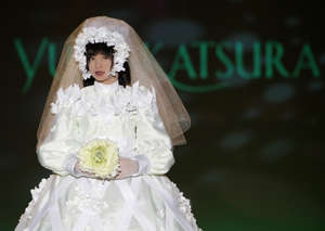 "The HRP-4C humanoid robot ""Miim"" presents a wedding dress by Japanese designer Yumi Katsura during the 2009 Yumi Katsura Paris Grand Collection in Osaka, western Japan, July 22, 2009. REUTERS/Toru Hanai (JAPAN ENTERTAINMENT SOCIETY SCI TECH)"