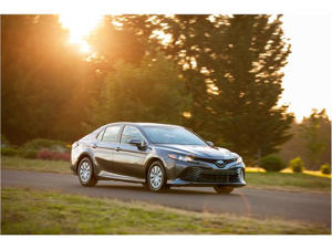 a car parked on the side of the road: 2018 Toyota Camry Hybrid