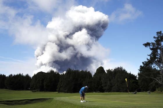 Slide 30 of 204: Doug Ralston plays golf in Volcano, Hawaii, as a huge ash plume rises from the summit of Kiluaea volcano Monday, May 21, 2018.