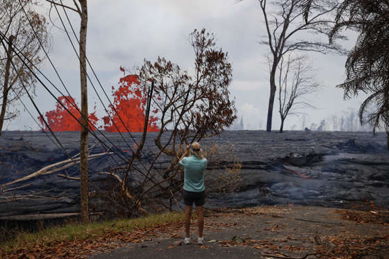 Slide 28 of 204: Jim Carpenter take pictures of lava erupting from fissures in the Leilani Estates subdivision near Pahoa, Hawaii, Tuesday, May 22, 2018. Authorities were racing Tuesday to close off production wells at a geothermal plant threatened by a lava flow from Kilauea volcano on Hawaii's Big Island