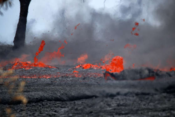 Slide 24 of 204: Fissures spew lava in the Leilani Estates subdivision near Pahoa, Hawaii, Tuesday, May 22, 2018. Authorities were racing Tuesday to close off production wells at a geothermal plant threatened by a lava flow from Kilauea volcano on Hawaii's Big Island.