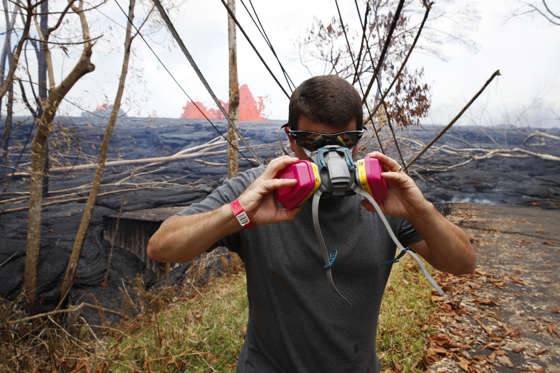 Slide 27 of 204: Heath Dalton removes his mask as lava erupts from fissures in the Leilani Estates subdivision near Pahoa, Hawaii, Tuesday, May 22, 2018. Authorities were racing Tuesday to close off production wells at a geothermal plant threatened by a lava flow from Kilauea volcano on Hawaii's Big Island
