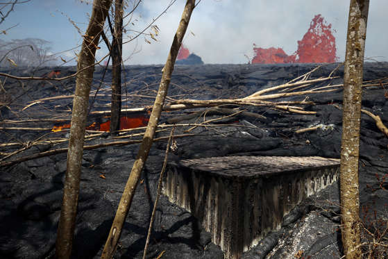 Slide 18 of 204: A property is devastated by lava as fissures continue to spew lava in the Leilani Estates subdivision near Pahoa, Hawaii, Tuesday, May 22, 2018.