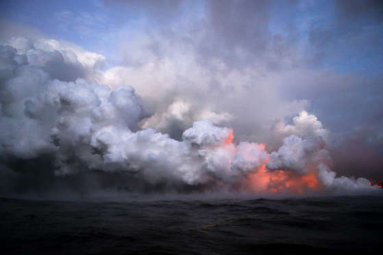 Slide 22 of 204: Steam plumes rise as lava glows (LOWER R) as it enters the Pacific Ocean at dawn, after flowing to the water from a Kilauea volcano fissure, on Hawaii's Big Island on May 22, 2018 near Pahoa, Hawaii.