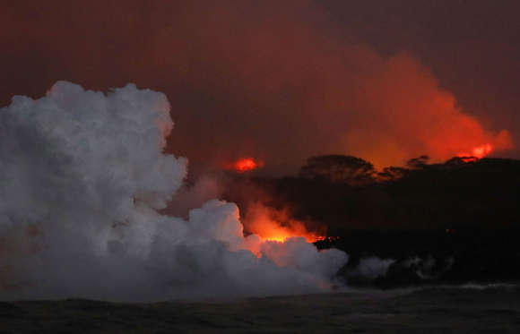 Slide 14 of 204: A steam plume rises as lava enters the Pacific Ocean at dawn, after flowing to the water from a Kilauea volcano fissure, on Hawaii's Big Island on May 22, 2018 near Pahoa, Hawaii.