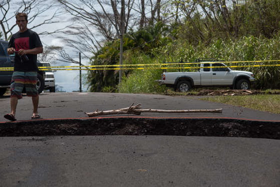 Slide 20 of 204: A resident of the Leilani Estates subdivision steps over a crack in Pahoa, Hawaii on May 22, 2018.