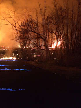 Slide 10 of 204: This photo released Wednesday, May 23, 2018 by the U.S. Geological Survey shows  blue burning flame of methane gas was observed in the cracks on Kahukai Street, during the overnight hours. The volcano produces methane when hot lava buries and burns plants and trees. Scientists say the methane can seep through cracks several feet away from the lava.