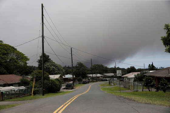 Slide 11 of 204: A volcanic ash cloud hovers in the distance over the small town of Pahala during the eruption of the Kilauea Volcano in Pahala, Hawaii, U.S., May 23, 2018.  REUTERS/Marco Garcia