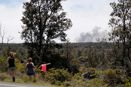 Slide 12 of 204: With an ash cloud visible from the Halemaumau crater, onlookers are seen from Highway 11 during the eruption of the Kilauea Volcano near Volcano, Hawaii, U.S., May 23, 2018.  REUTERS/Marco Garcia