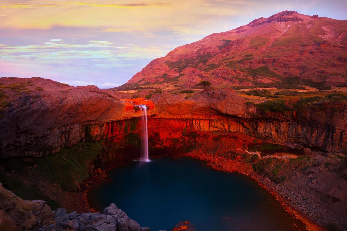 Diapositiva 5 de 51: Un atardecer cubre de rojo el Valle del Río Agrio y su caída, el Salto del Agrio, en Argentina.