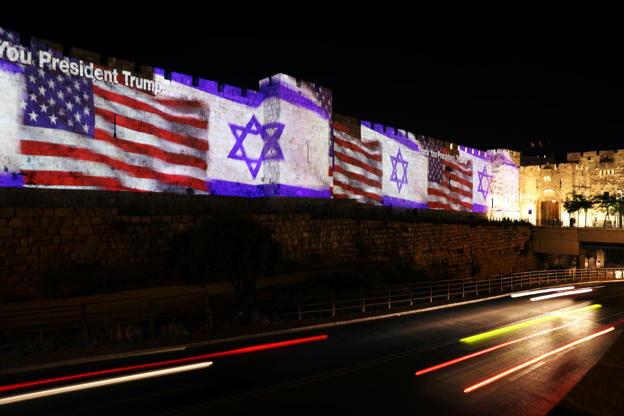 Slide 1 of 81: The U.S. and Israeli national flags are projected on a part of the walls surrounding Jerusalem's Old City, Israel May 14, 2018. REUTERS/Ammar Awad