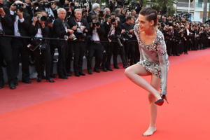 "TOPSHOT - US actress and member of the Feature Film Jury Kristen Stewart removes her shoes on the red carpet as she arrives on May 14, 2018 for the screening of the film ""BlacKkKlansman"" at the 71st edition of the Cannes Film Festival in Cannes, southern France. (Photo by Valery HACHE / AFP)        (Photo credit should read VALERY HACHE/AFP/Getty Images)"