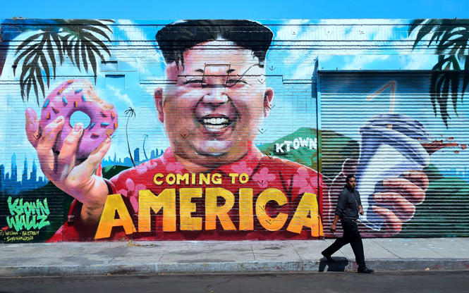 Slide 3 of 138: A pedestrian walks past a mural titled 'Coming To America' depicting North Korean leader Kim Jong-un holding a donut and milkshake by graffiti artsists @welinoo, @balstroem and @sorenarildsen in Los Angeles, California on May 14, 2018, created as part of the Ktown Wallz Project in the city's Koreatown neighborhod. - US President Donald Trump is scheduled to meet with North Korean leader Kim Jong Un on June 12, 2018 in Singapore. (Photo by Frederic J. BROWN / AFP) / RESTRICTED TO EDITORIAL USE - MANDATORY MENTION OF THE ARTIST UPON PUBLICATION - TO ILLUSTRATE THE EVENT AS SPECIFIED IN THE CAPTION        (Photo credit should read FREDERIC J. BROWN/AFP/Getty Images)