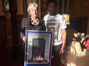 Handout photo dated 10/05/18 issued by Relative Justice Humanity for Grenfell of Prime Minister Theresa May with artist Damel Carayol, who lost his niece in the Grenfell Tower fire.