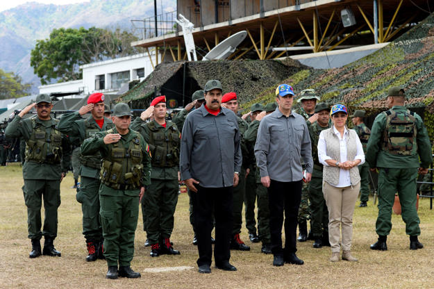 Venezuelan President Nicolas Maduro (2nd-L), First Lady Cilia Flores (R) and Vice President Tarek El Aissami (2nd-R) receive military honors upon their arrival for the military exercises at Fort Tiuna in Caracas on February 24, 2018. / AFP PHOTO / FEDERICO PARRA        (Photo credit should read FEDERICO PARRA/AFP/Getty Images)