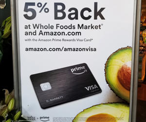 Sign at Whole Foods market grocery store in San Ramon, California announcing promotion in which Amazon Prime credit card holders receive a 5% discount when shopping at the store, February 27, 2018. On August 28, 2017, Amazon completed its acquisition of the upscale grocery chain.