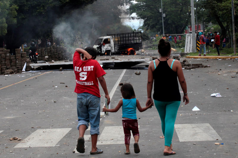 A family walks towards a burning truck during clashes between anti-government protesters and riot police in Masaya, Nicaragua May 15, 2018. REUTERS/Oswaldo Rivas