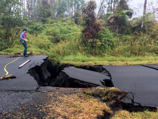 Slide 2 of 106: HVO geologist next to cracks on Nohea Street in Leilani Estates this morning. These cracks expanded significantly in the past day. Note the vertical offset across the cracks.