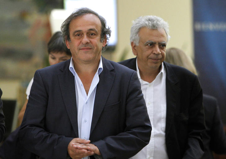 FILE - In this Wednesday, Sept. 21, 2011 file photo, UEFA President Michel Platini, left, walks with Cyprus Football Association President Costakis Koutsokoumnis, during a UEFA summit in southern port city of Limassol, Cyprus. Koutsokoumnis, the president of the Cyprus Football Association for the last 17 years, has died at 61. The Cyprus FA said on its Website that Koutsokoumnis died Monday, March 5, 2018, after a months-long battle with cancer. (AP Photo/Petros Karadjias, File)